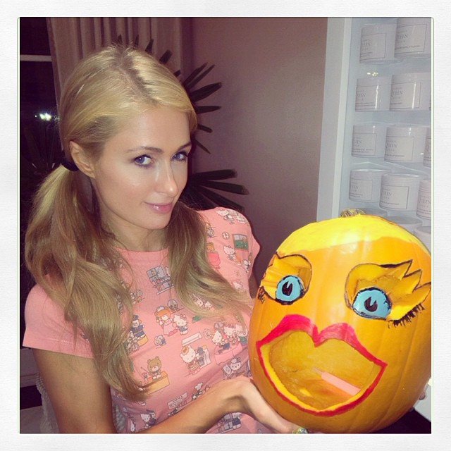 Paris Hilton grüsst mit einem Kürbis.